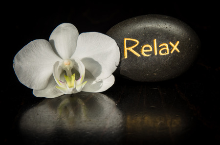word relax written on lava stone and white orchid photo
