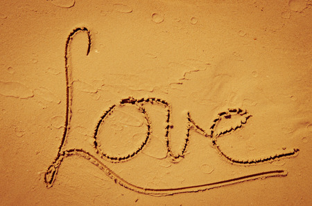 word love written into sand on beach photo