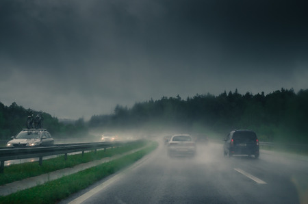 雨で道路上の車