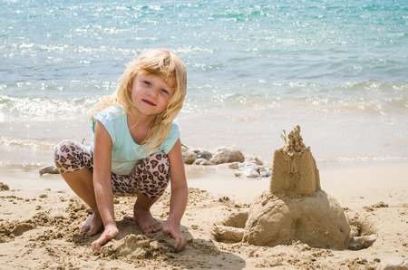children sandcastle: girl playing with sand in the beach Stock Photo
