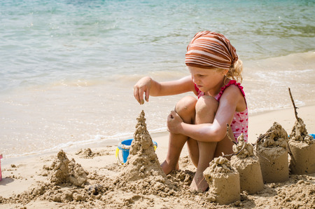girl playing with sand in the beach photo