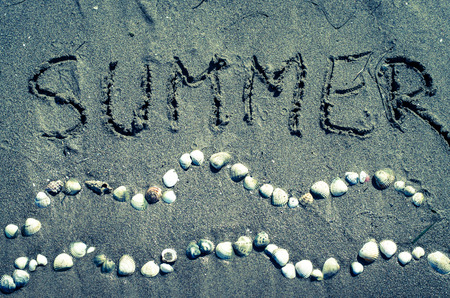 waves from shells and summer word on sand on beach photo