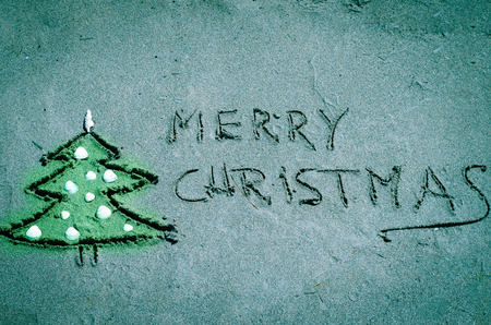 Christmas tree drawn into sand on beach photo