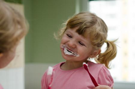 blond child girl brushing teeth photo