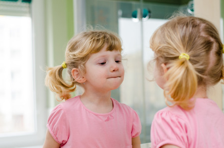 child watching itselt in the mirror