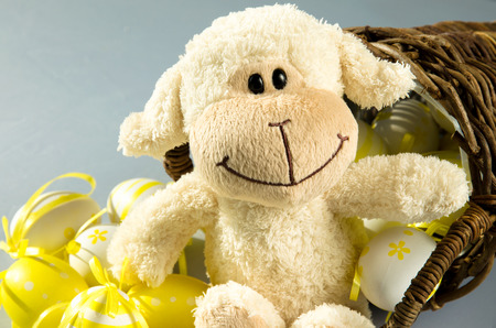 group of yellow easter eggs in wooden basket and white sheep photo