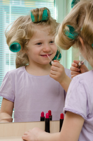 make up model: Blond child with lipstick and curlers in long hair