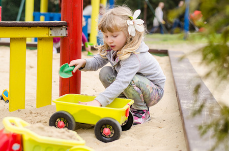 beautiful blond girl child playing on the playground photo