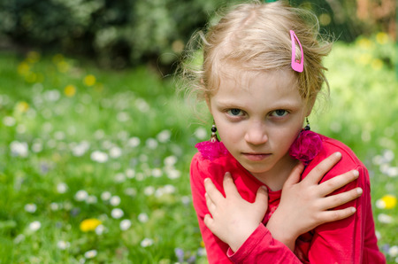 beautiful blond girl with crossed hands and dramatic view in floral meadow