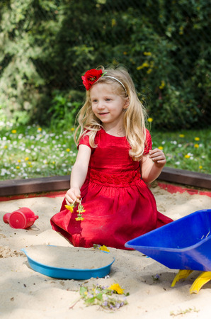 sandpit: adorable blond girl playing in sandpit Stock Photo