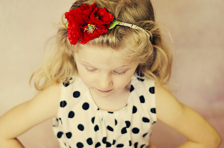 corn flower: small girl with closed eyes and red corn poppy flower in hair Stock Photo