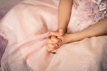 child praying: child with praying hands over pink dress image Stock Photo