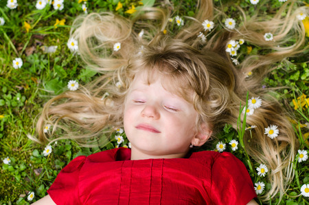 beautiful blond girl with closed eyes lying over green grass with daisies photo