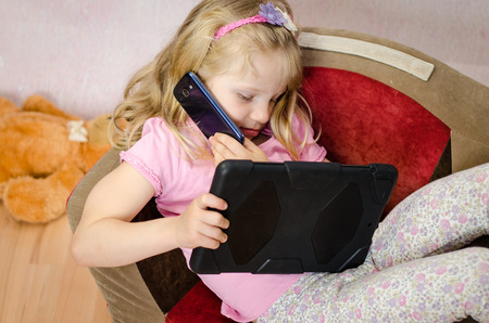 little blond girl speaking by mobile phone with tablet in hands photo