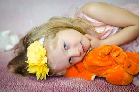plush: beautiful girl lying and holding plush toy