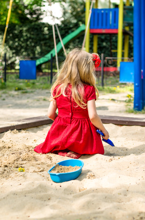 sandpit: blond girl with long hair rear view playing in sandpit Stock Photo