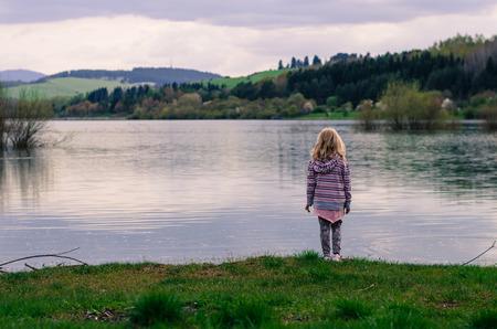 ni�os abandonados: chica rubia de pie en la orilla del agua del estanque en la tarde