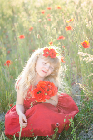 corn flower: beautiful blond girl with red corn poppy flower haze effect