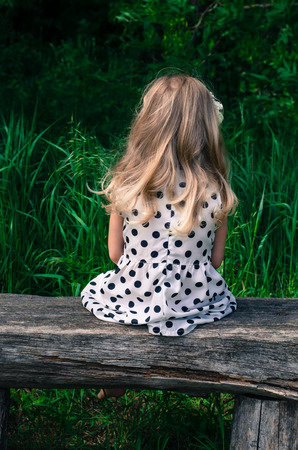 wood nymph: back view of blond girl in dotted dress sitting on bench