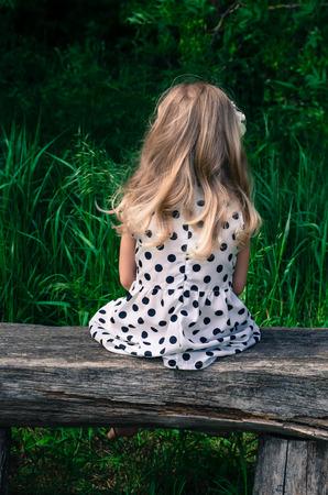 ni�os abandonados: vista trasera de una ni�a rubia en vestido de puntos sentado en el banco