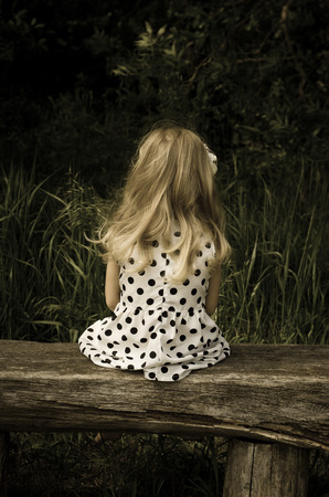 back view of blond girl in dotted dress sitting on bench photo