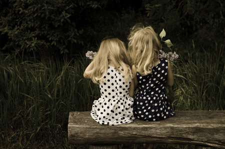 back view of blond girls in dotted dress sitting on bench photo