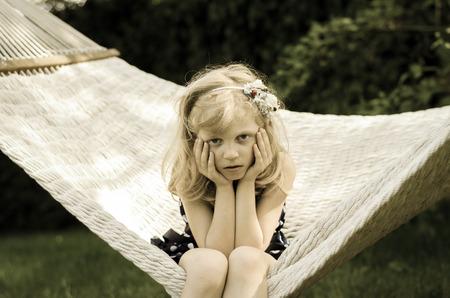 niños abandonados: hermosa chica rubia sentada en la hamaca blanca