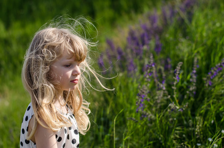 dress blowing in the wind: beautiful blond girl in green meadow with flowers