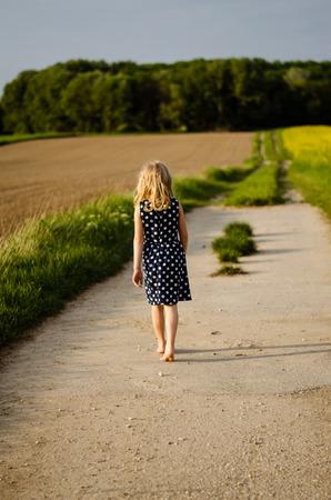 shoeless: blond girl walking in path between fields