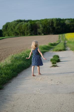 ni�os abandonados: chica rubia caminando en camino entre los campos