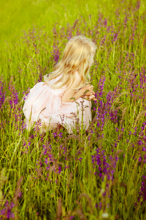 angel alone: beautiful little girl in pink flowers back view Stock Photo