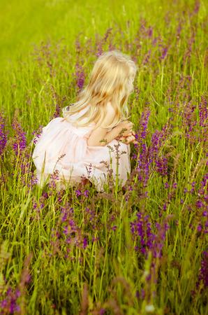 niños abandonados: hermosa niña en flores rosadas visión posterior
