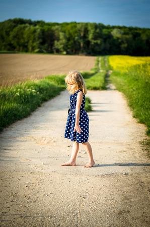 blond girl dancing in rural path Standard-Bild