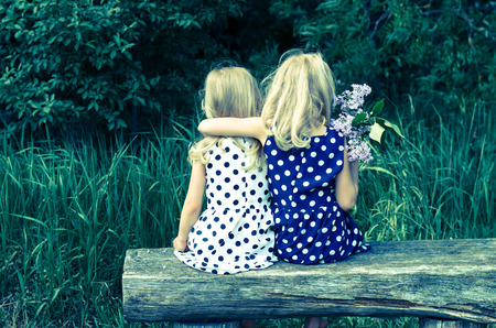two  blond girls sitting on bench back view