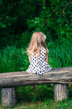 girl with long blond hair sitting in bench and waiting photo