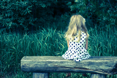 girl with long blond hair sitting in bench and waiting filtered effect back view photo