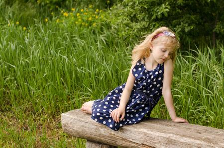 blond girl: beautiful sad blond girl sitting in bench