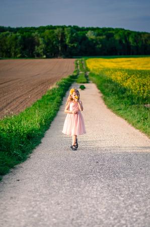 shoeless: girl in pink dress walking in rural path