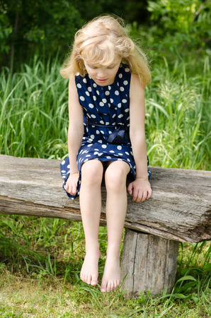 sad girl with long blond hair sitting in bench and waiting photo