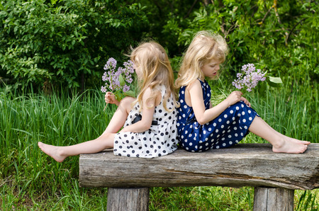 wood nymph: two beautiful blond girls sitting on bench in meadow Stock Photo