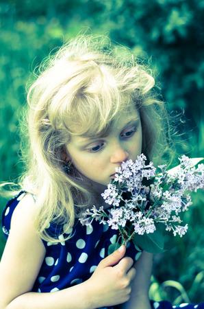 girl holding flower: portrait of beautiful sad blond girl holding flower