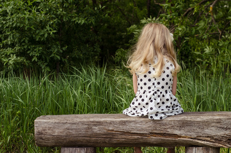 girl with long blond hair sitting in bench and waiting back view photo