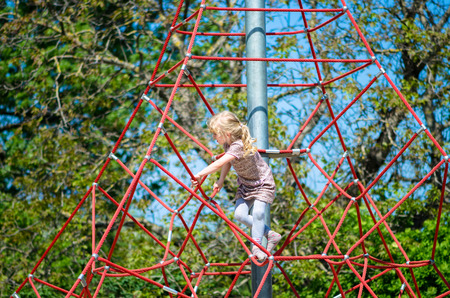 girl climbing up on a playground