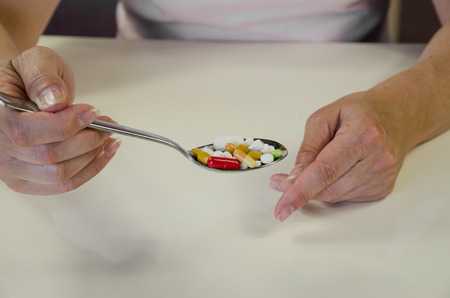 human hand with spoon full of colorful medicals photo