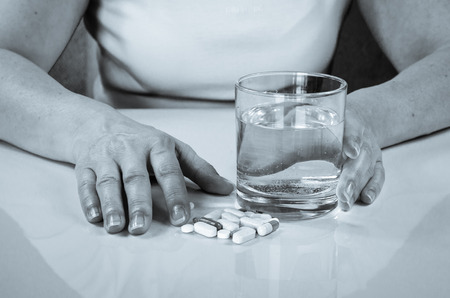 megrim: person holding pill and glass of water