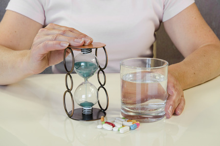 megrim: person holding pill,sandglass and glass of water