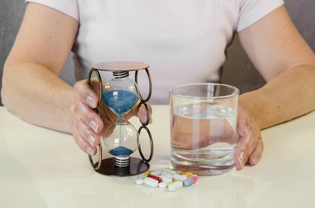 megrim: person holding pill, sandglass and glass of water