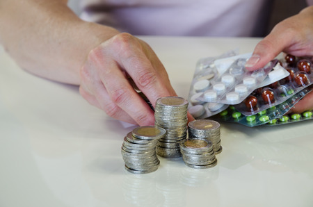 hand with coins of money and blisters with pills photo