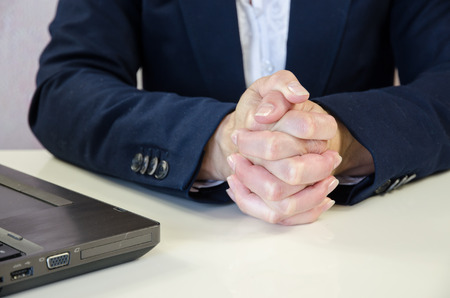 clenched hands over white office desk