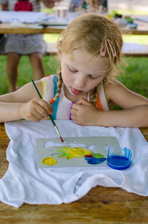 blond girl: blond girl sitting and painting with brush